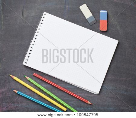Blank notepad and colorful pencils on blackboard background. Top view with copy space