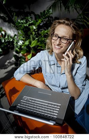 Beautiful young businesswoman using mobile phone while working at laptop