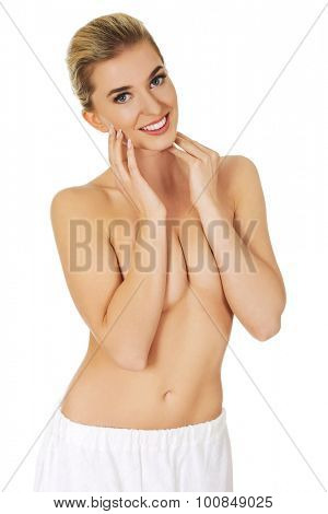 Young beautiful smile topless woman with white towel around her waist