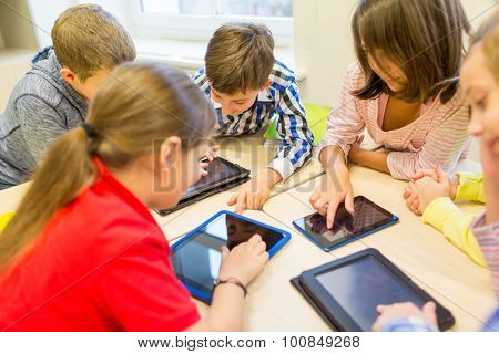 education, elementary school, learning, technology and people concept - group of school kids with tablet pc computer having fun and playing on break in classroom