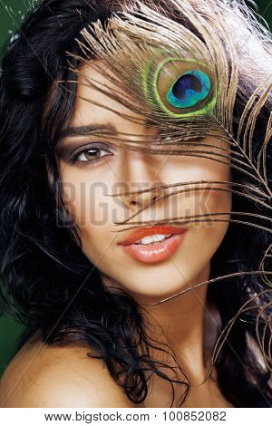 young sensitive brunette woman with peacock feather eyes close up