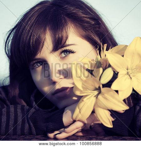 Happy young woman with flowers daydreaming outdoor