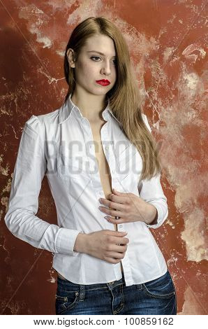 Young slim beautiful young blond woman with long legs and hair in shirt and jeans
