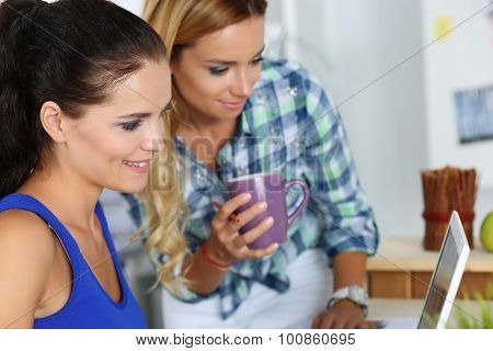 Two Female Designers In Office Looking At Laptop