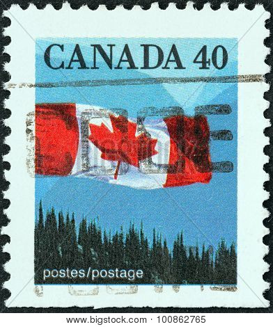 CANADA - CIRCA 1989: A stamp printed in Canada shows flag over forest