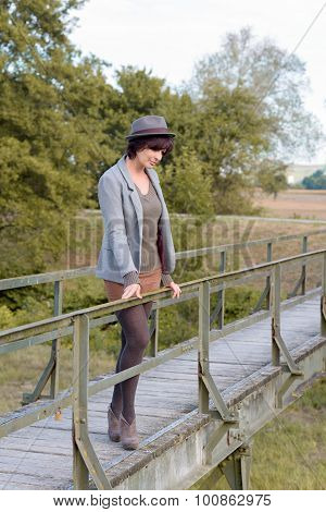 Contemplative Trendy Young Woman On A Footbridge