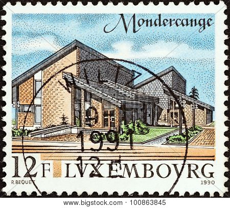 LUXEMBOURG - CIRCA 1990: A stamp printed in Luxembourg shows Mondercange administrative offices
