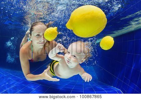 Little Child With Mother Swimming Underwater In Pool