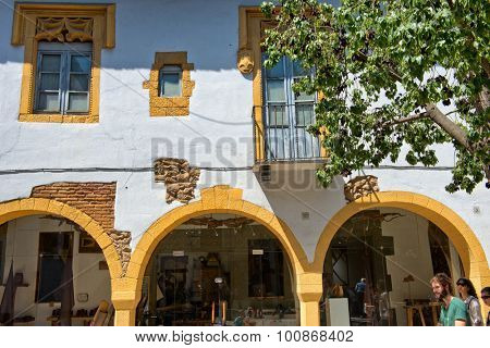 BARCELONA, SPAIN - MAY 02: Architectural Detail of Yellow Building Archways in Sunny Plaza, Poble Espanyol Museum District, Barcelona, Spain. May 02, 2015.