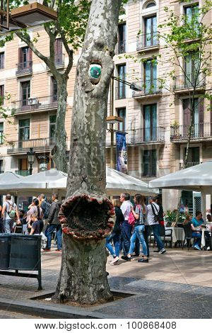 BARCELONA, SPAIN - MAY 02: Tree Trunk Painted to Look Like Monster with Open Mouth and Single Eye on Bustling La Rambla Pedestrian Promenade in Barcelona, Spain. May 02, 2015.