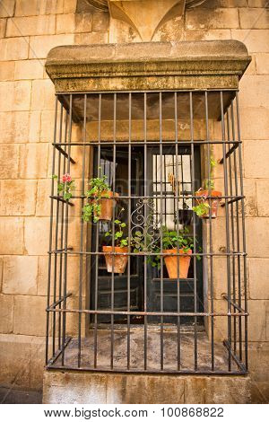 BARCELONA, SPAIN - MAY 02: Detail of Doorway with Flower Pots Hanging from Security Bars Surrounding Small Balcony, Historic Building in Poble Espanyol Museum Area, Barcelona, Spain. May 02, 2015.