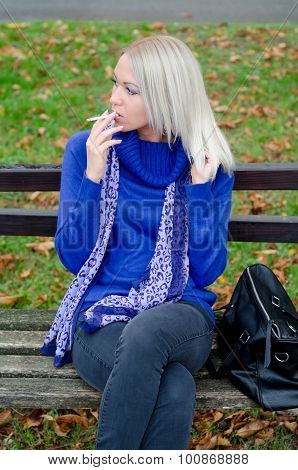 Young Woman Sitting In The Park And Smoking Cigarette