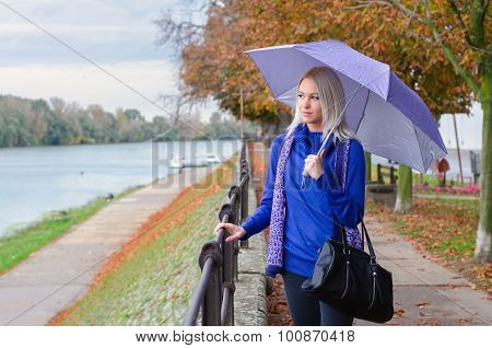 Beautiful Young Woman Walking Beside River On Rainy Autumn Day