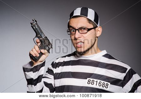 Young prisoner with weapon against gray