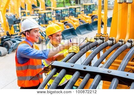 Asian motor mechanic discussing with engineer task list in construction machine workshop