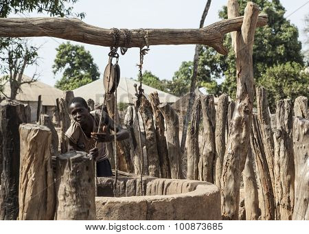 Young african boy getting water from a manual well