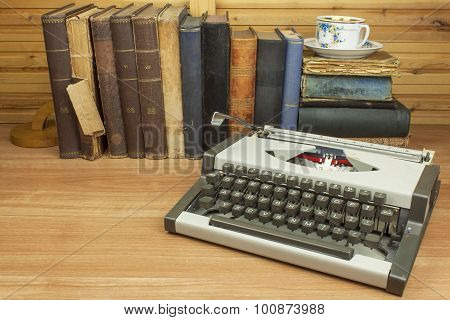 Travel typewriter on the desk of the writer. The writer writes a novel.