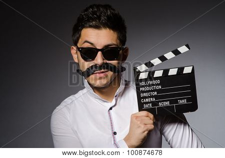 Young caucasian man with clapperboard against gray