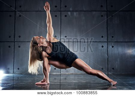 Strong woman bodybuilder stretching on wall background.