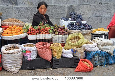 woman is selling fruits and spicery on the market in Lijiang