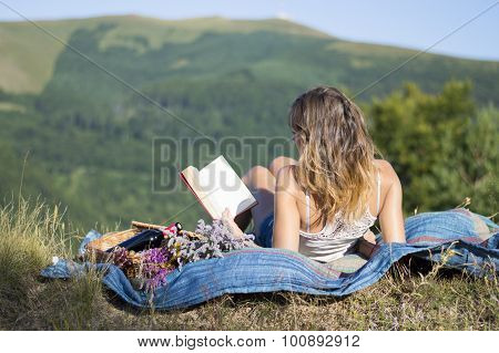Girl Laying On A Blanket And Reading A Book On A Picnic In The Field