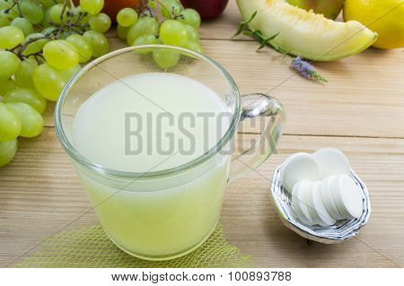 Effervescent Tablets And Dissolved Tablet In A Glass With Bunch Of Fruit On The Table