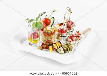 Close-up View Set Of Canapes With Vegetables, Salami, Seafood, Meat And Decoration On Whie Plate Stu