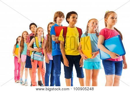 Kids standing in the line holding textbooks