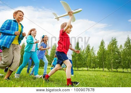 Small boy holds white airplane toy and kids behind