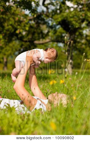 Mother playing with baby on meadow