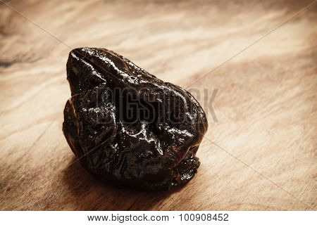 Single Dried Plum Prune On Wooden Table