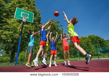 Teens in jump playing basketball game together