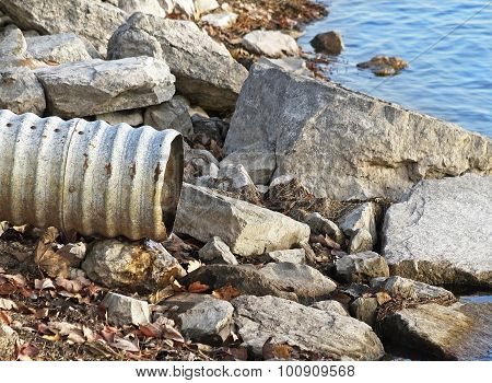Large metal drain pipe on rocky shore line of lake