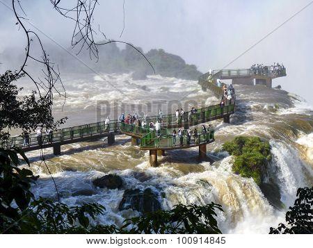 Tourists Admire Iguacu (iguazu) Falls On A Border Of Brazil And Argentina