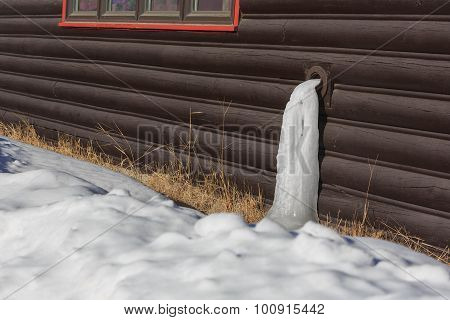 Icy Water Pipe And Wooden House
