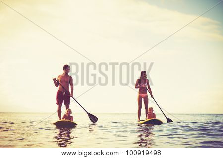 Family Having Fun Stand Up Paddling Together in the Ocean at Sunrise