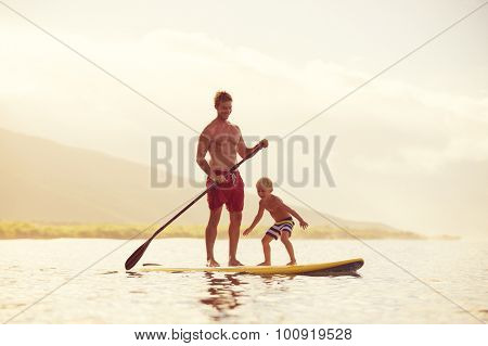 Father and Son Stand Up Paddling at Sunrise