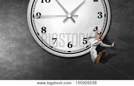 Concept of time with jumping businesswoman over big alarm clock