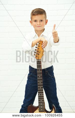 Little boy with guitar on light background