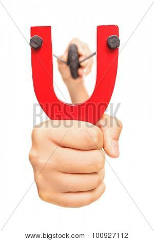 Hand holding a stretched slingshot with a rock in it isolated on white background