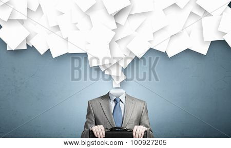 Faceless businessman and many papers instead of his head