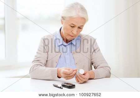 medicine, age, diabetes, health care and people concept - senior woman with glucometer and test stripes checking blood sugar level at home