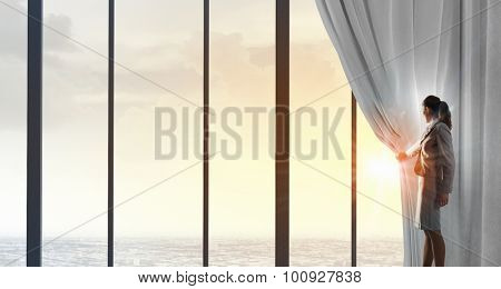 Businesswoman pulling curtain and cityscape behind it