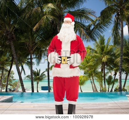 christmas, holidays, travel and people concept - man in costume of santa claus over swimming pool on tropical beach background