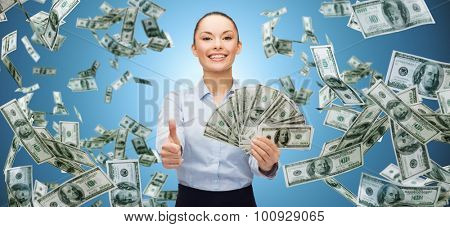 business, money, finance, people and banking concept - smiling businesswoman with heap of dollar cash money showing thumbs up over blue background