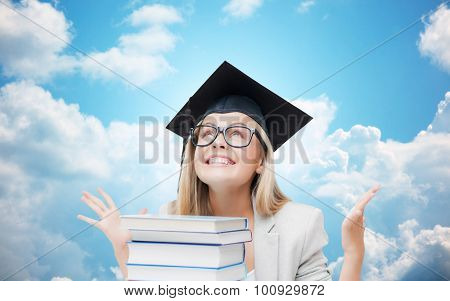 education, school, knowledge, graduation and people concept - happy student girl in bachelor cap with books over blue sky and clouds background