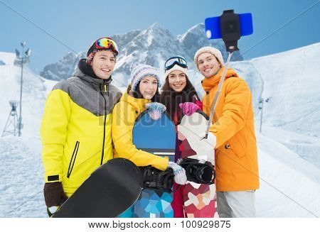 winter sport, leisure, friendship, technology and people concept - happy friends with snowboards and smartphone taking selfie over snow and mountain background