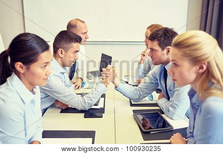 business, people, crisis and confrontation concept - smiling business team sitting on opposite sides and arm wrestling in office