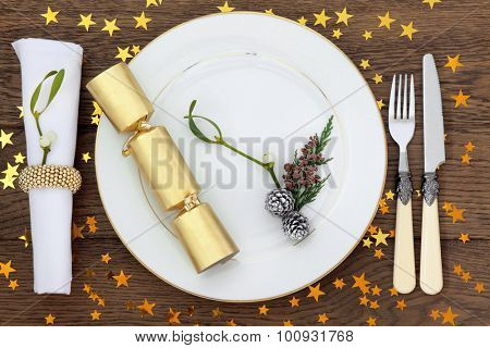 Christmas holiday dinner place setting with plate, napkin, cutlery, mistletoe, cracker and gold stars over oak table background.