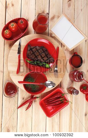 red theme lunch : fresh grilled bbq roast beef steak red plate green chili tomato soup ketchup sauce paprika small jug glass ground pepper american peppercorn modern cutlery served wooden plate table